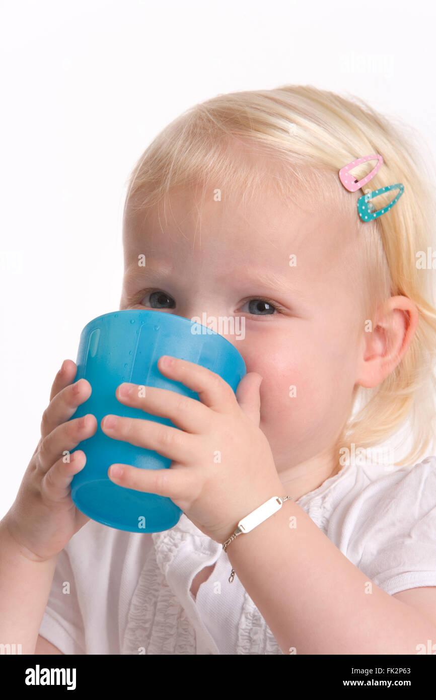 5134a9d1cfc8f Niño Niña está bebiendo de un vaso de plástico azul sobre fondo blanco.  Imagen De
