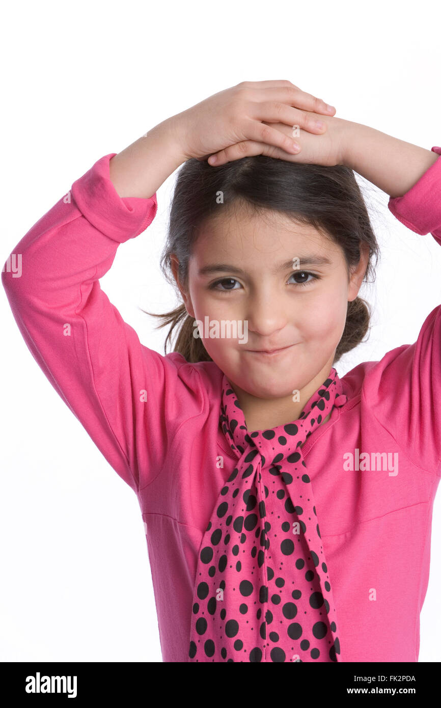 Niña está mirando a la cámara con una expresión tímida sobre fondo blanco. Imagen De Stock