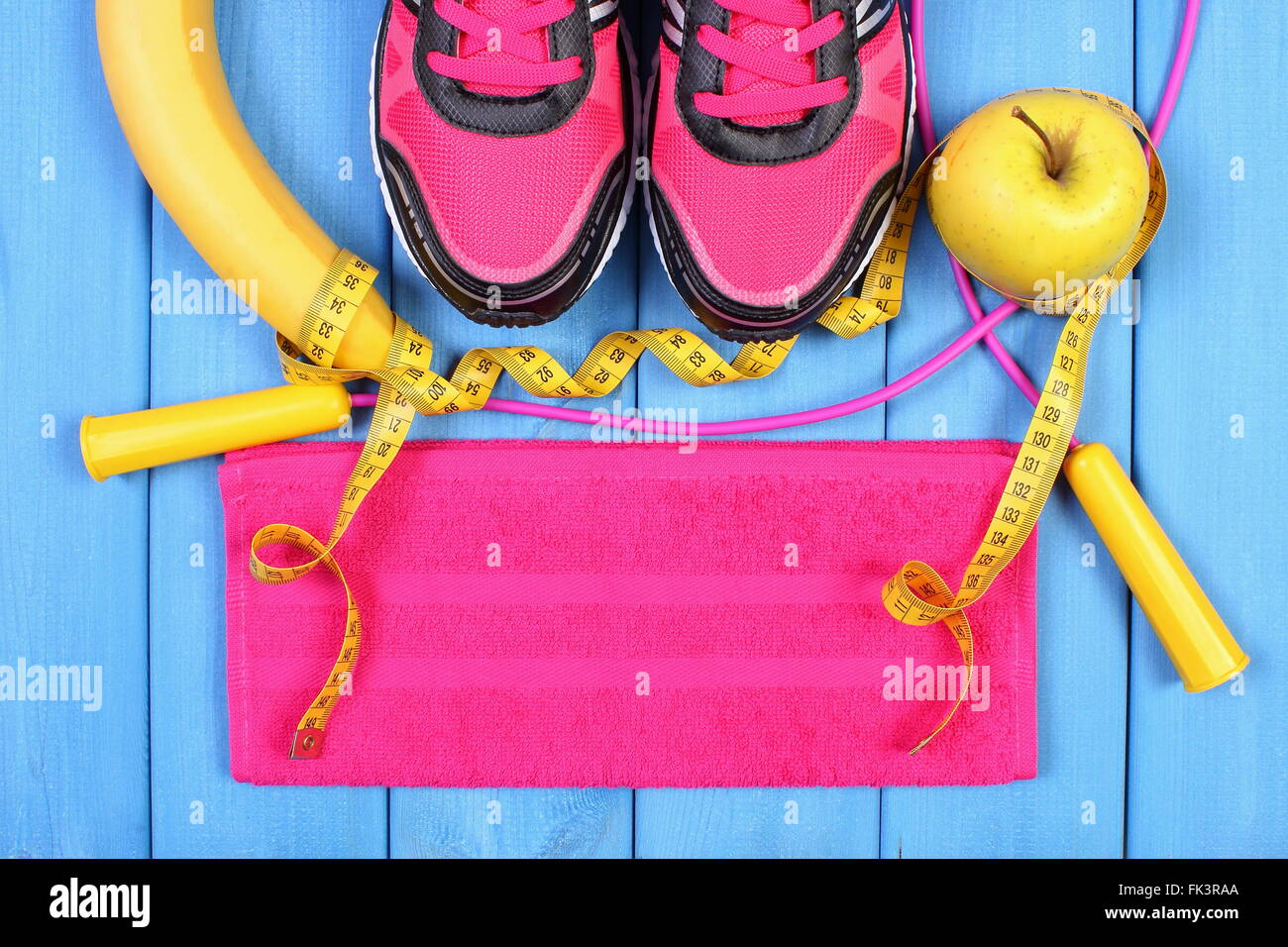 Par de zapatillas de deporte, frutas frescas y accesorios para hacer ejercicios o deporte sobre placas de azul, Imagen De Stock