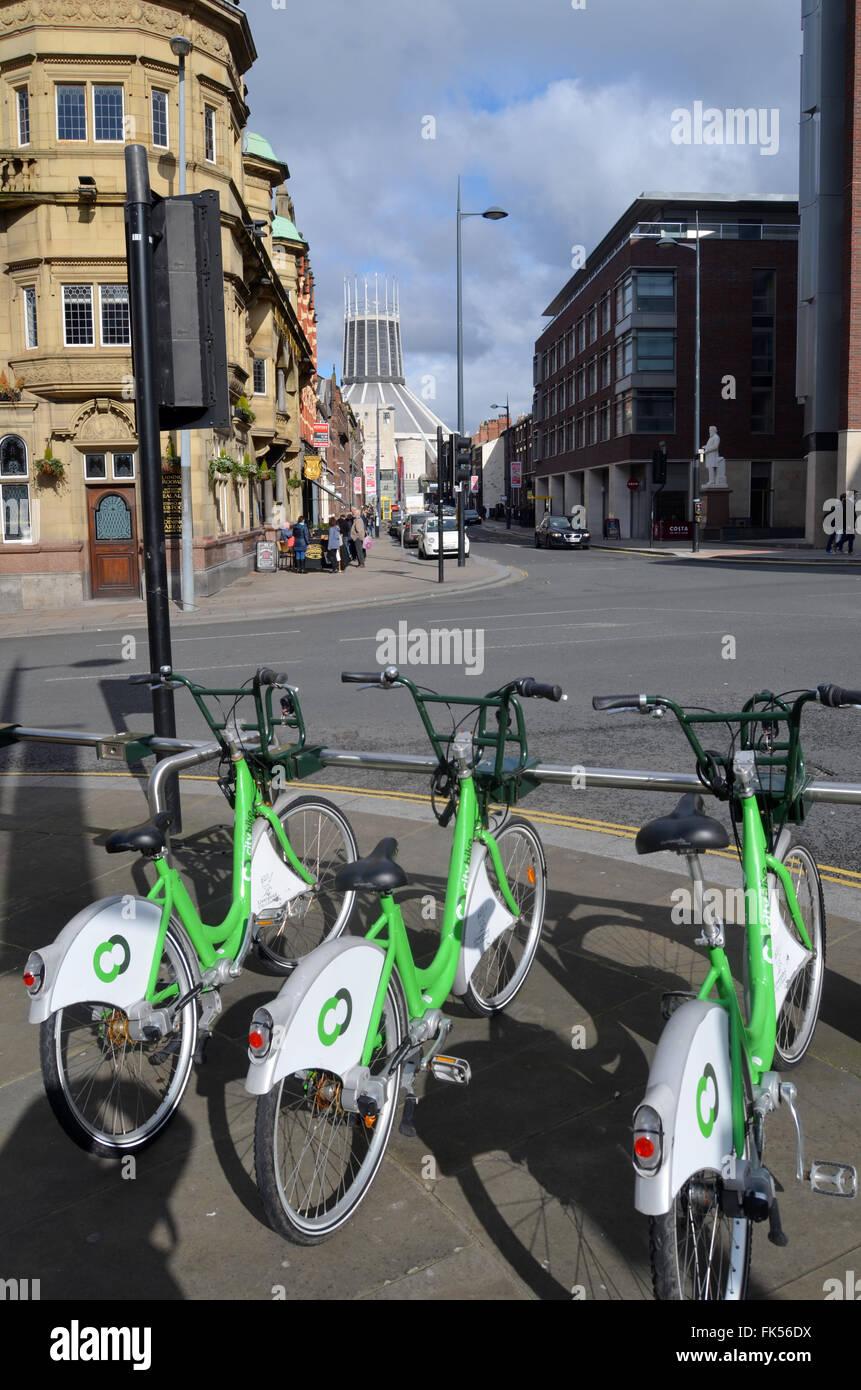 Alquiler de bicicletas Citybike scheme, Liverpool, en marzo de 2016, la catedral católica en el fondo Imagen De Stock