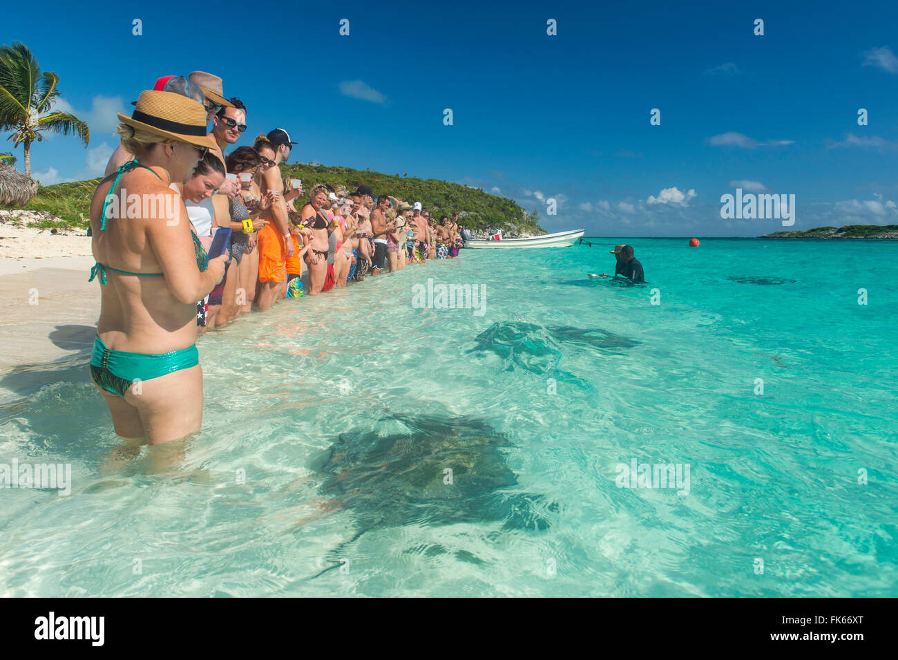 Los turistas de pie sobre una playa de arena blanca con rayas nadando en las aguas color turquesa, Exumas, Bahamas, Foto de stock
