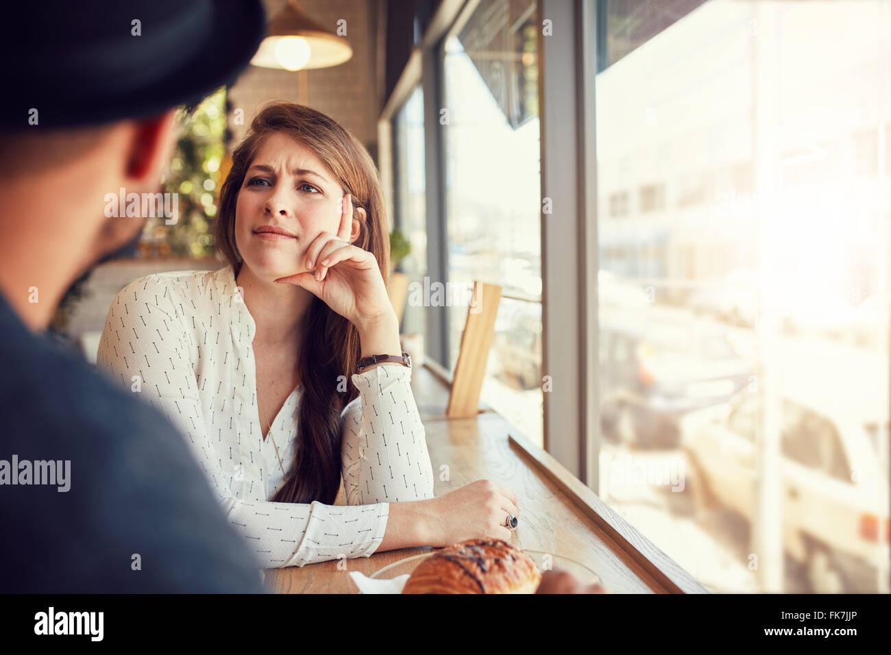 Hermosa joven sentado en un café y mirando a su novio. Pareja joven en la cafetería. Imagen De Stock