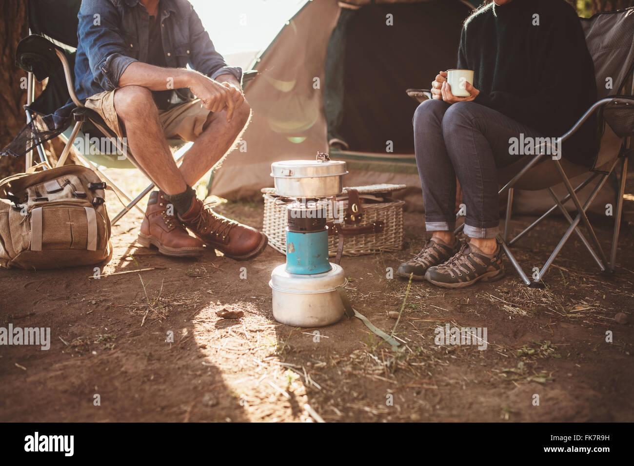 Captura recortada de pareja sentados alrededor de una estufa para acampar. Hombre y mujer sentada en una silla fuera Imagen De Stock