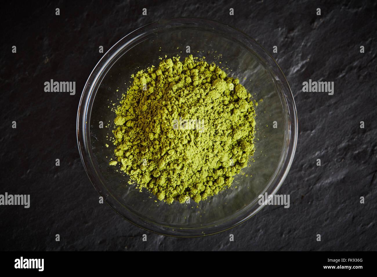 Polvo Matcha verde en un tazón de vidrio en la placa de piedra negra Foto de stock