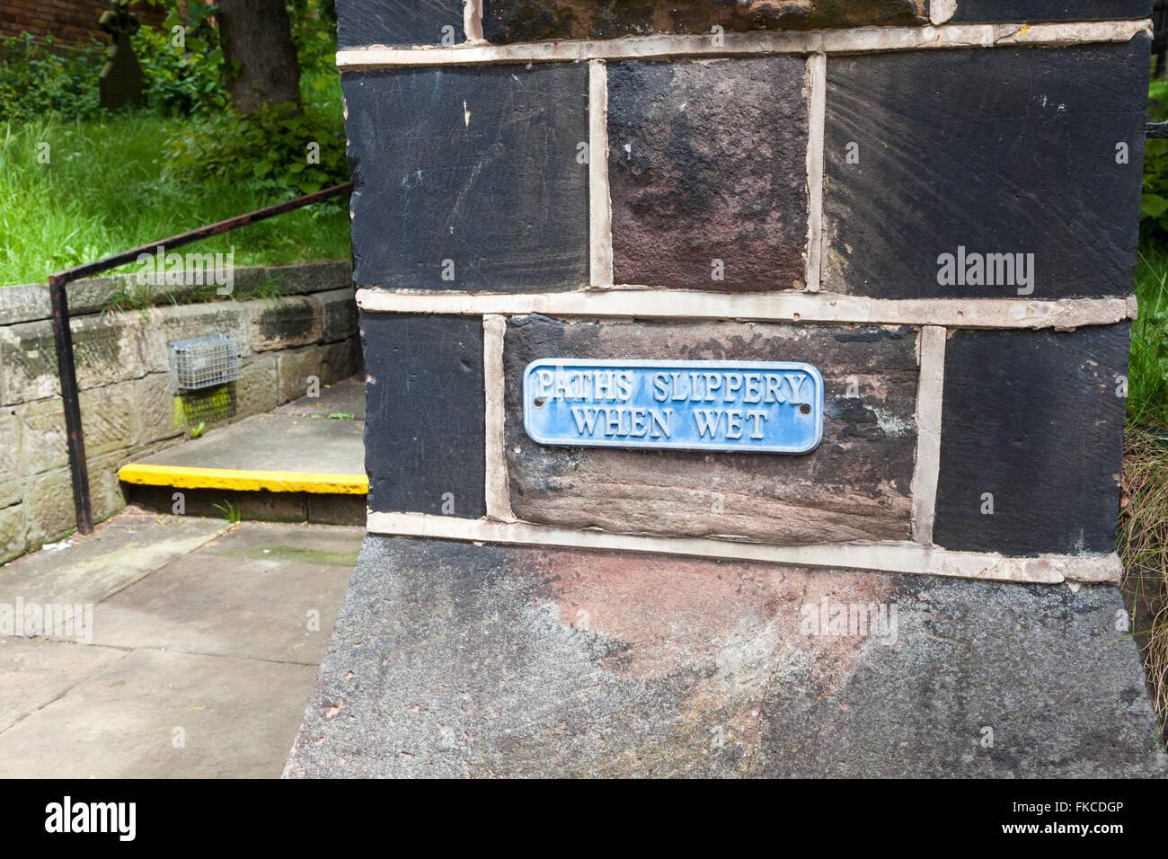 Un cartel junto a una ruta de acceso y los pasos señalando caminos slippery when wet Imagen De Stock