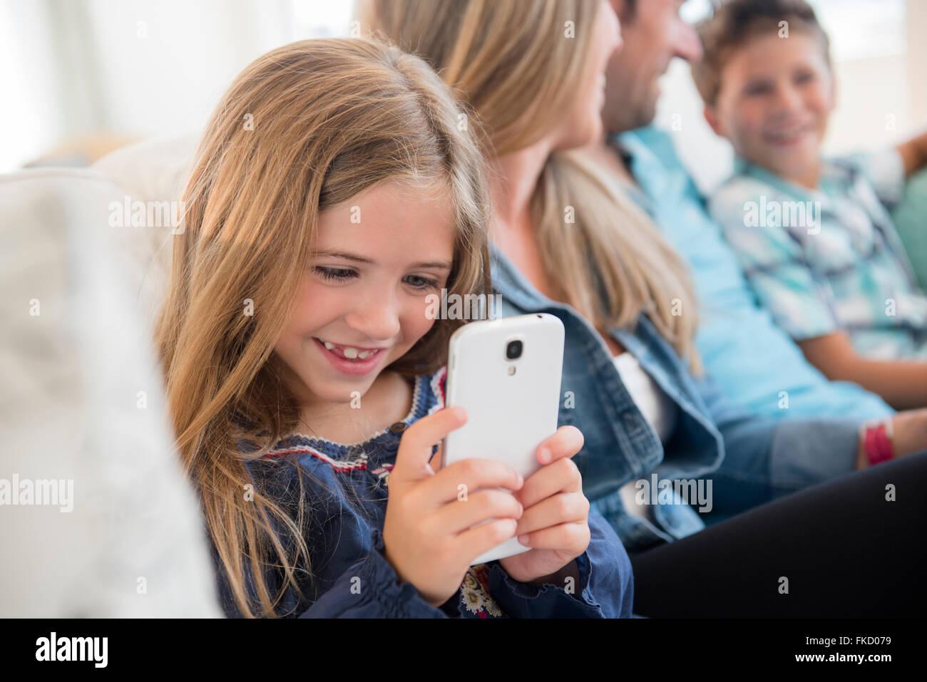Chica (6-7) sentado en el sofá, usando teléfonos inteligentes. Imagen De Stock