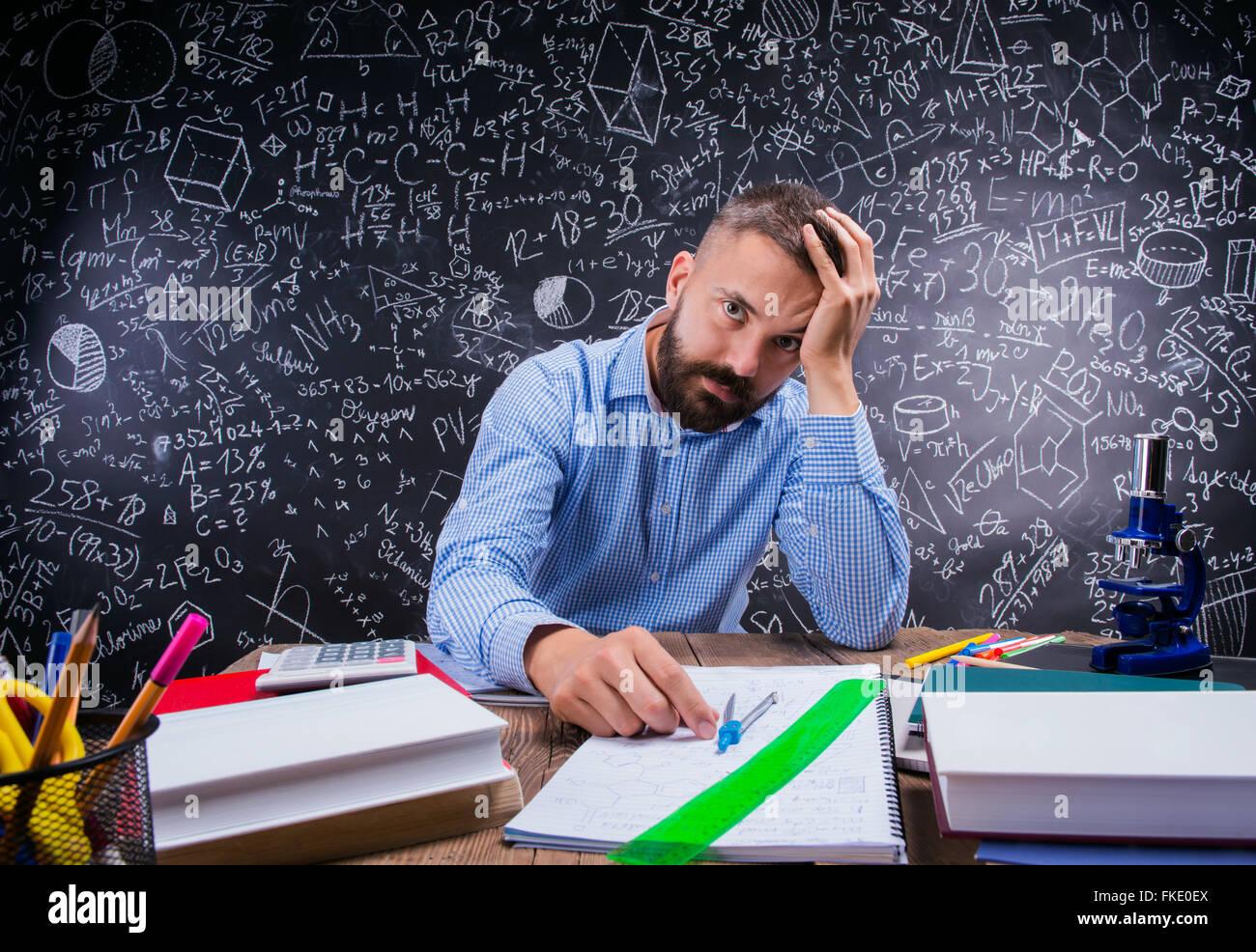 Malestar docente en escritorio, material escolar, sosteniendo la ...