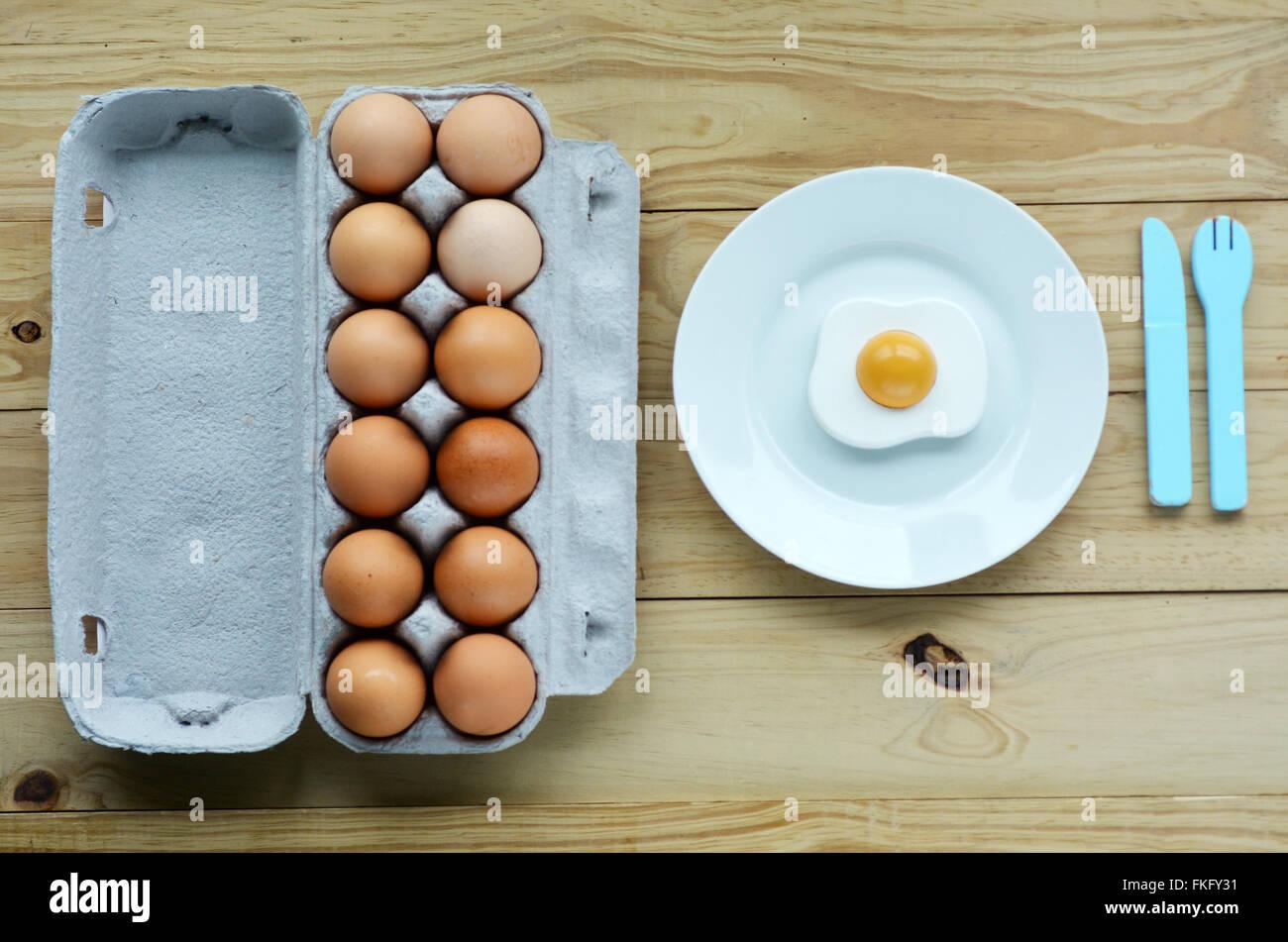 Sentar planas de huevos en bandeja junto a una placa blanca con sunny side up huevo y cuchillo y tenedor de madera.Fondo Imagen De Stock