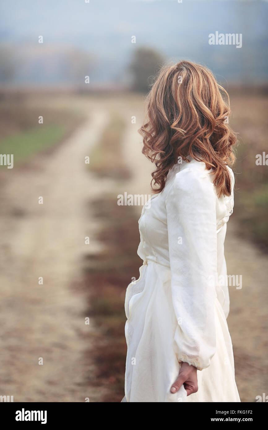 Mujer con vestido de novia vintage mirar país por carretera . Pureza e inocencia Imagen De Stock