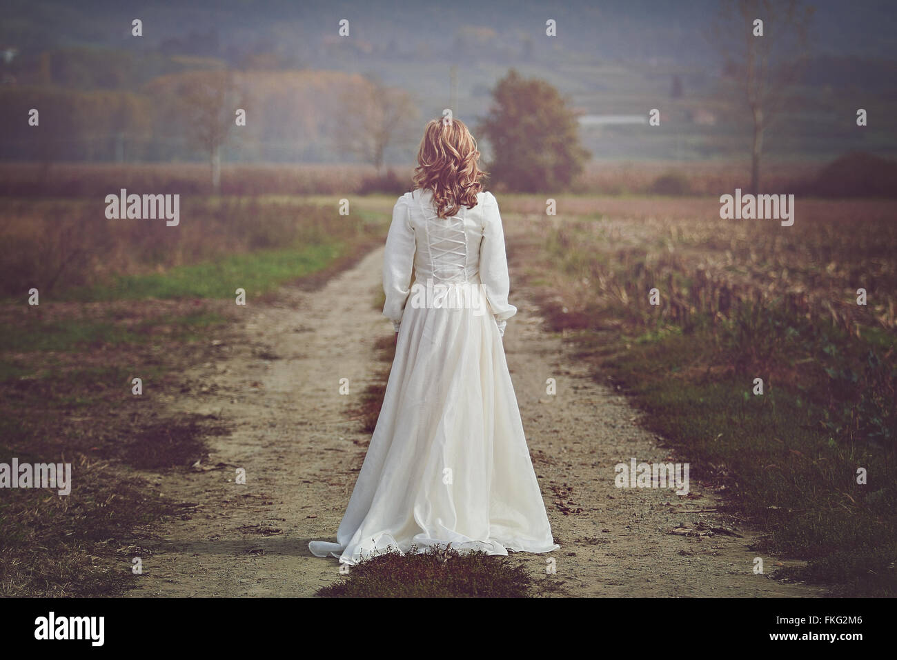 Novia vestidos con hermosos campos en el país. Pureza e inocencia Imagen De Stock