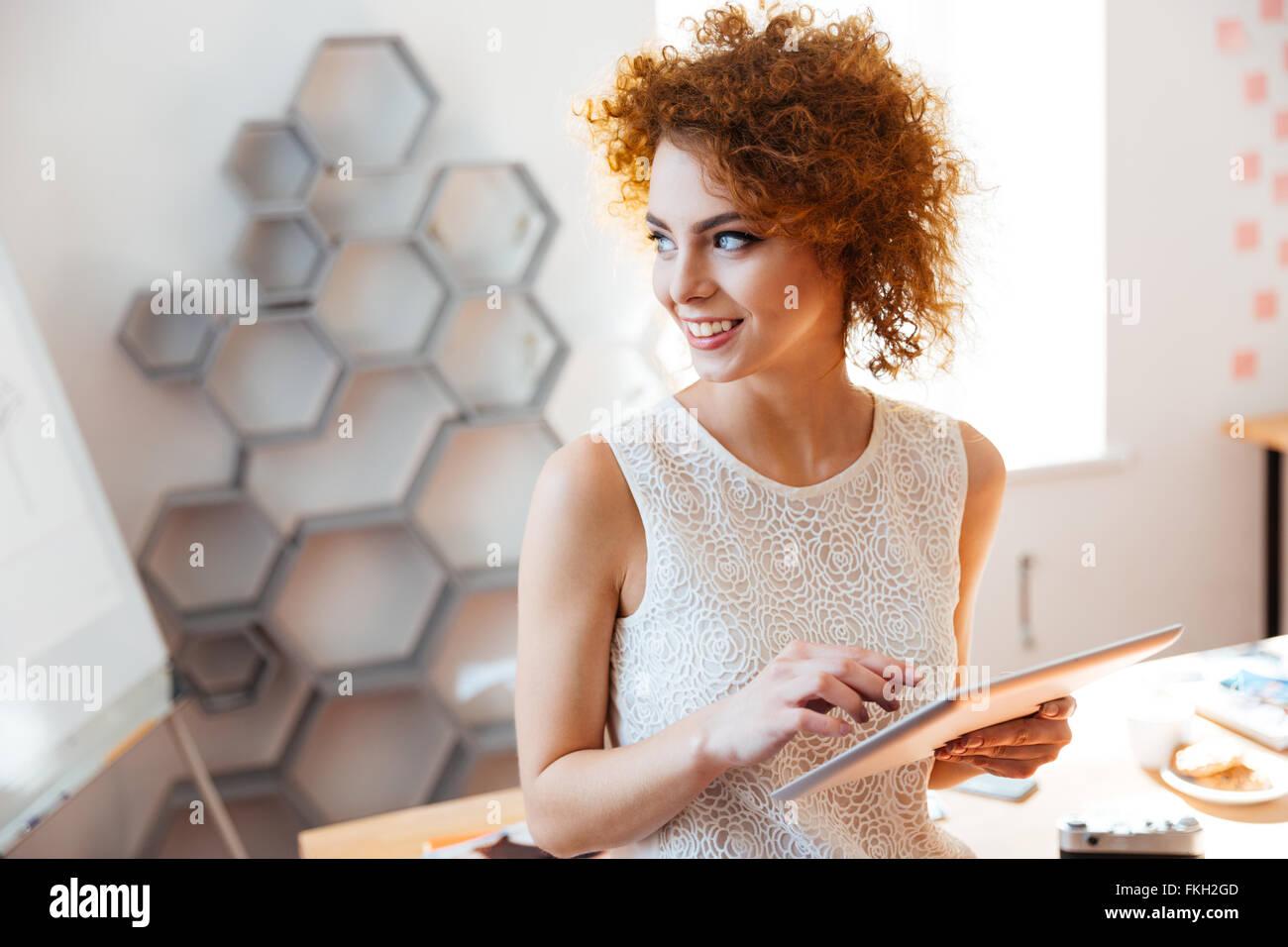 Lindo alegre curly empresa joven mujer de pie y con tablet en Office Imagen De Stock