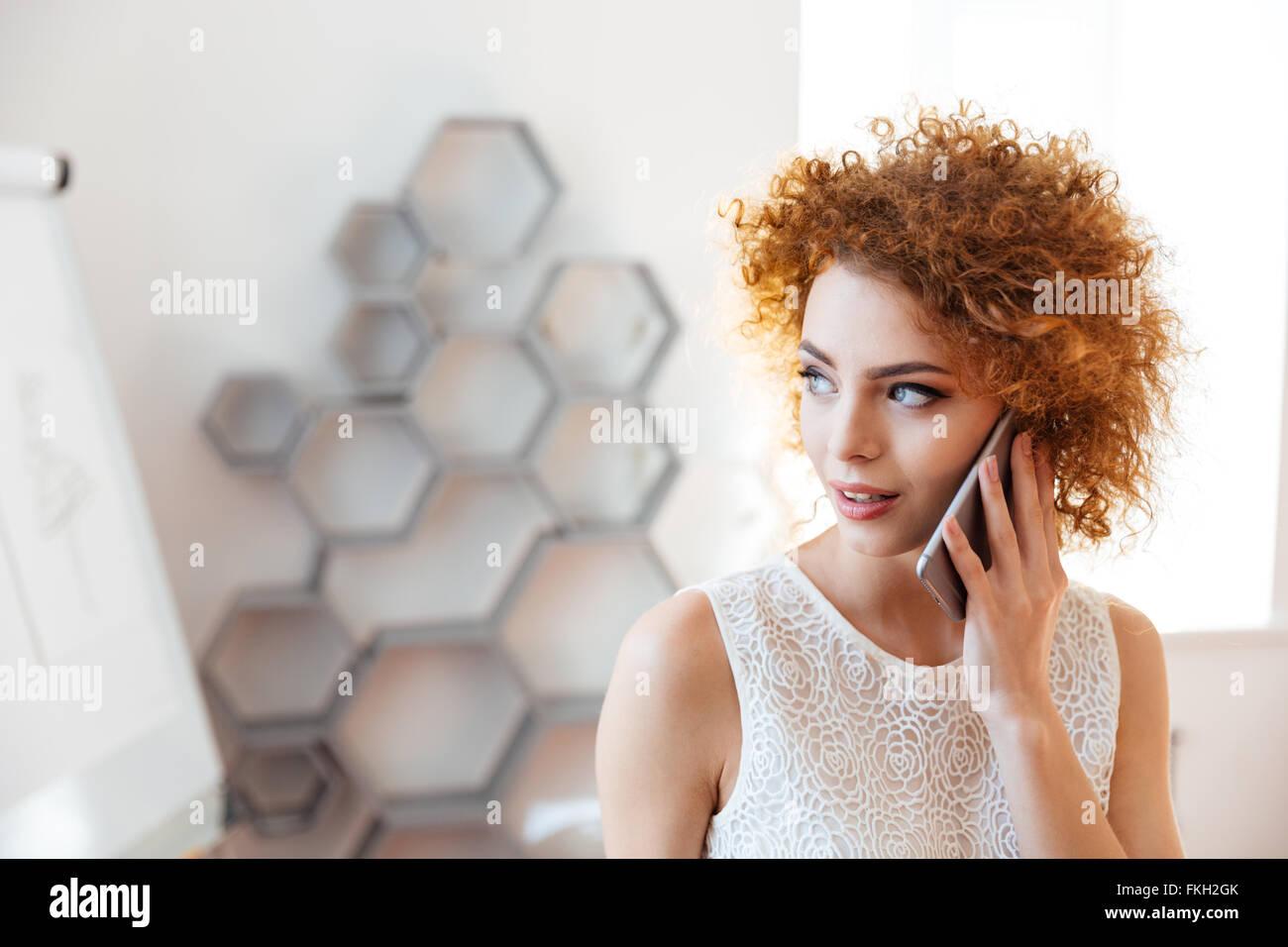 Pensativo joven y bella mujer de negocios hablando por teléfono celular en la oficina Foto de stock