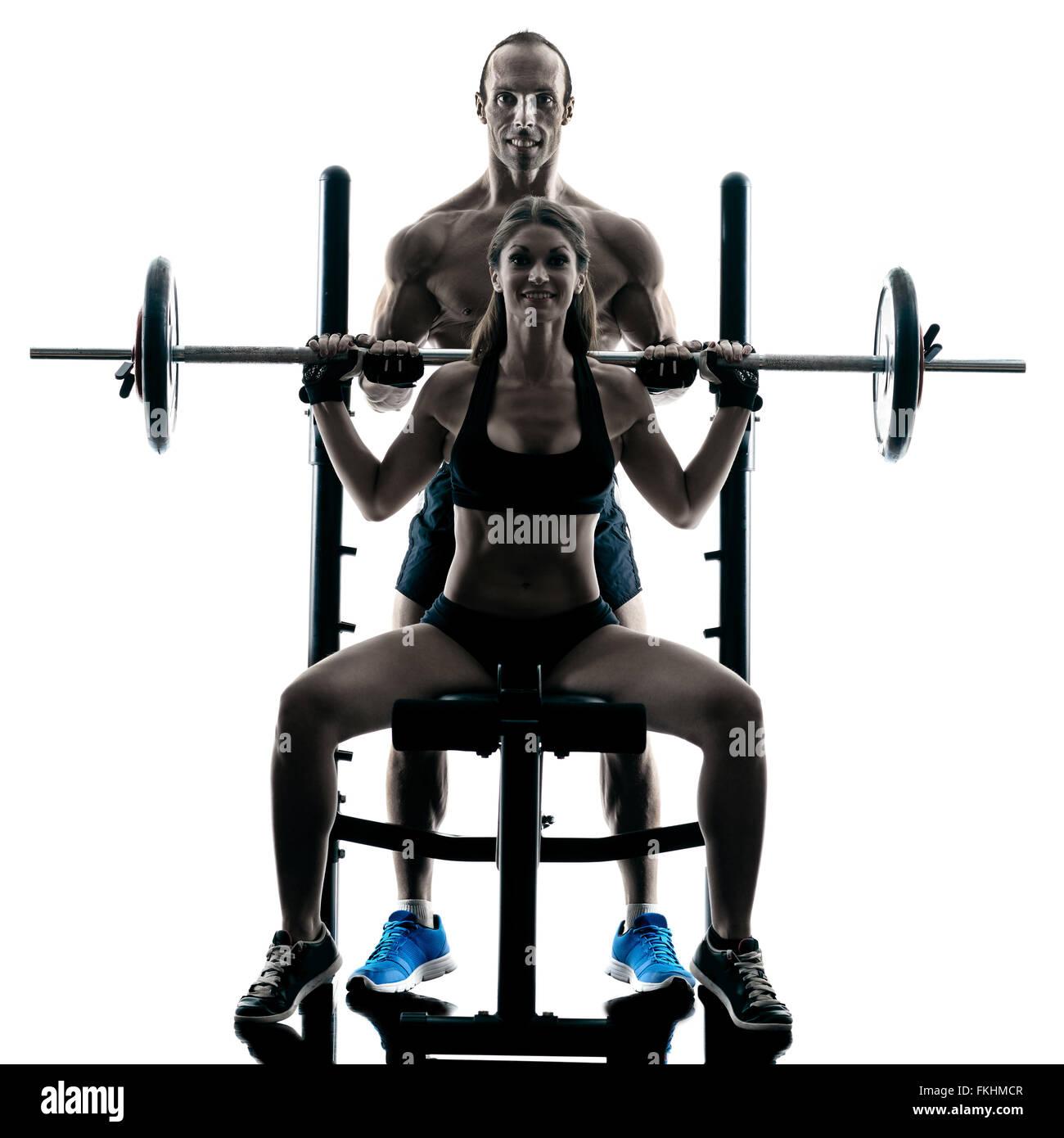 Una pareja caucásica ejercicio gimnasio body building ejercicios en studio en silueta aislado Imagen De Stock