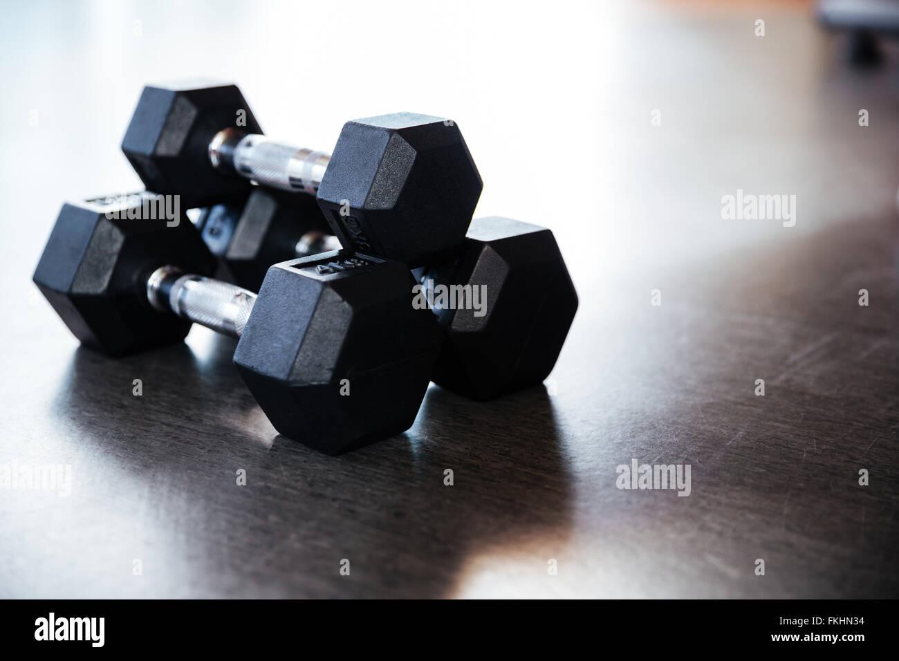 Primer plano de tres pesas de metal en el piso en el gimnasio Imagen De Stock