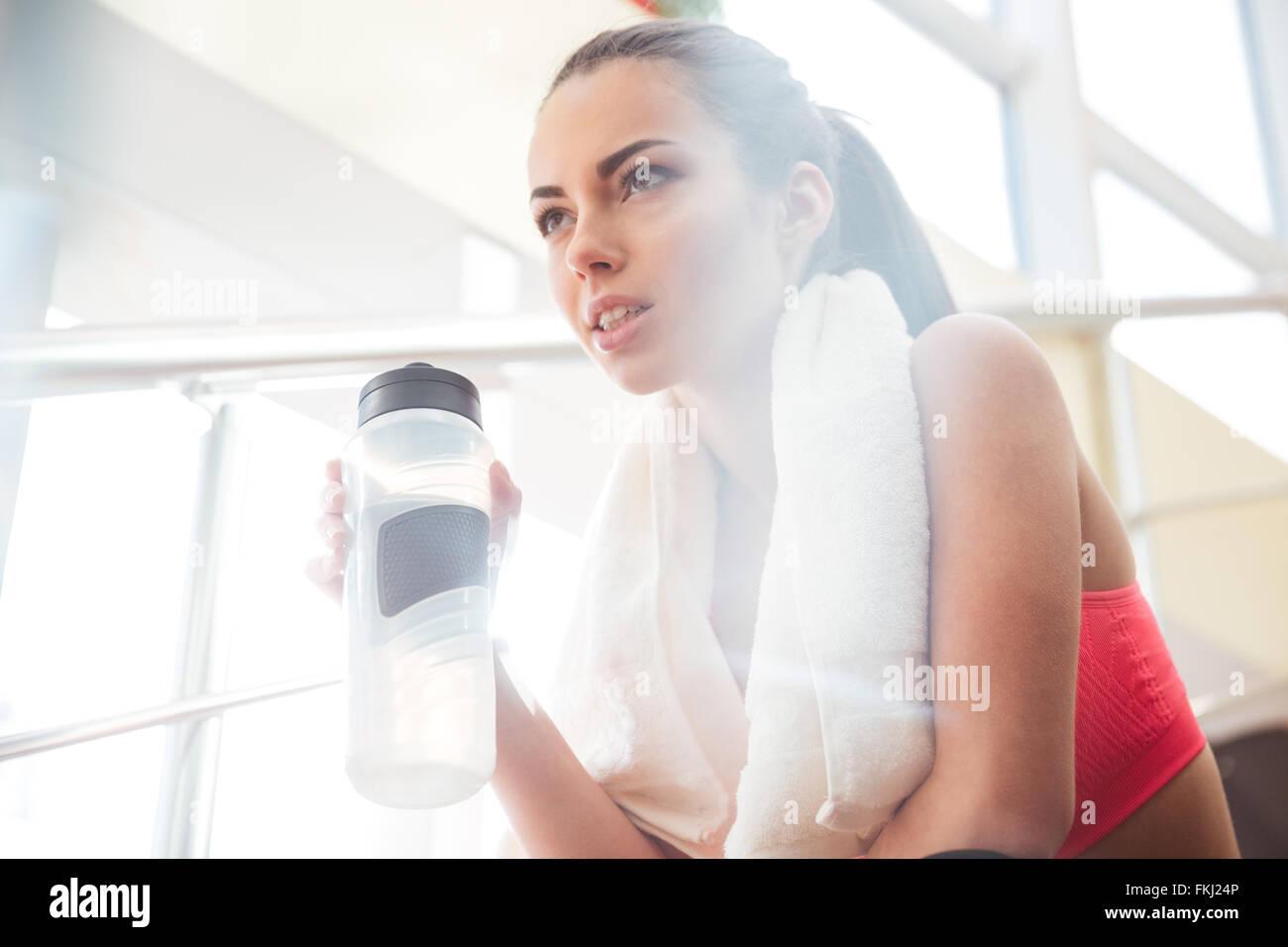 Guapa joven sportswoman relajante después de la capacitación y el suministro de agua potable en el gimnasio Imagen De Stock