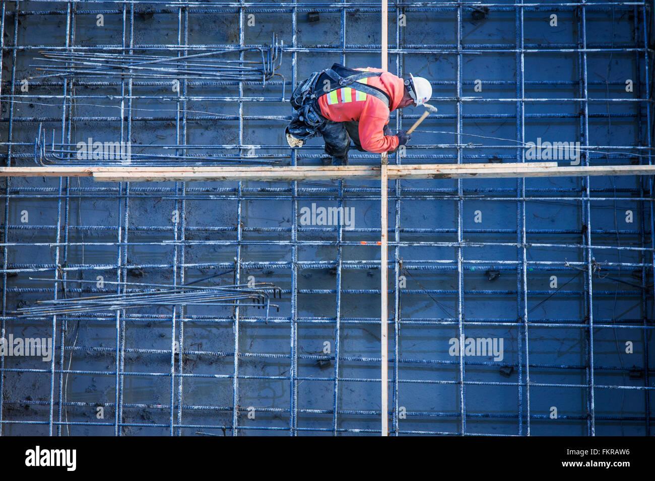 Trabajador caucásico clavando tablones en sitio en construcción Foto de stock