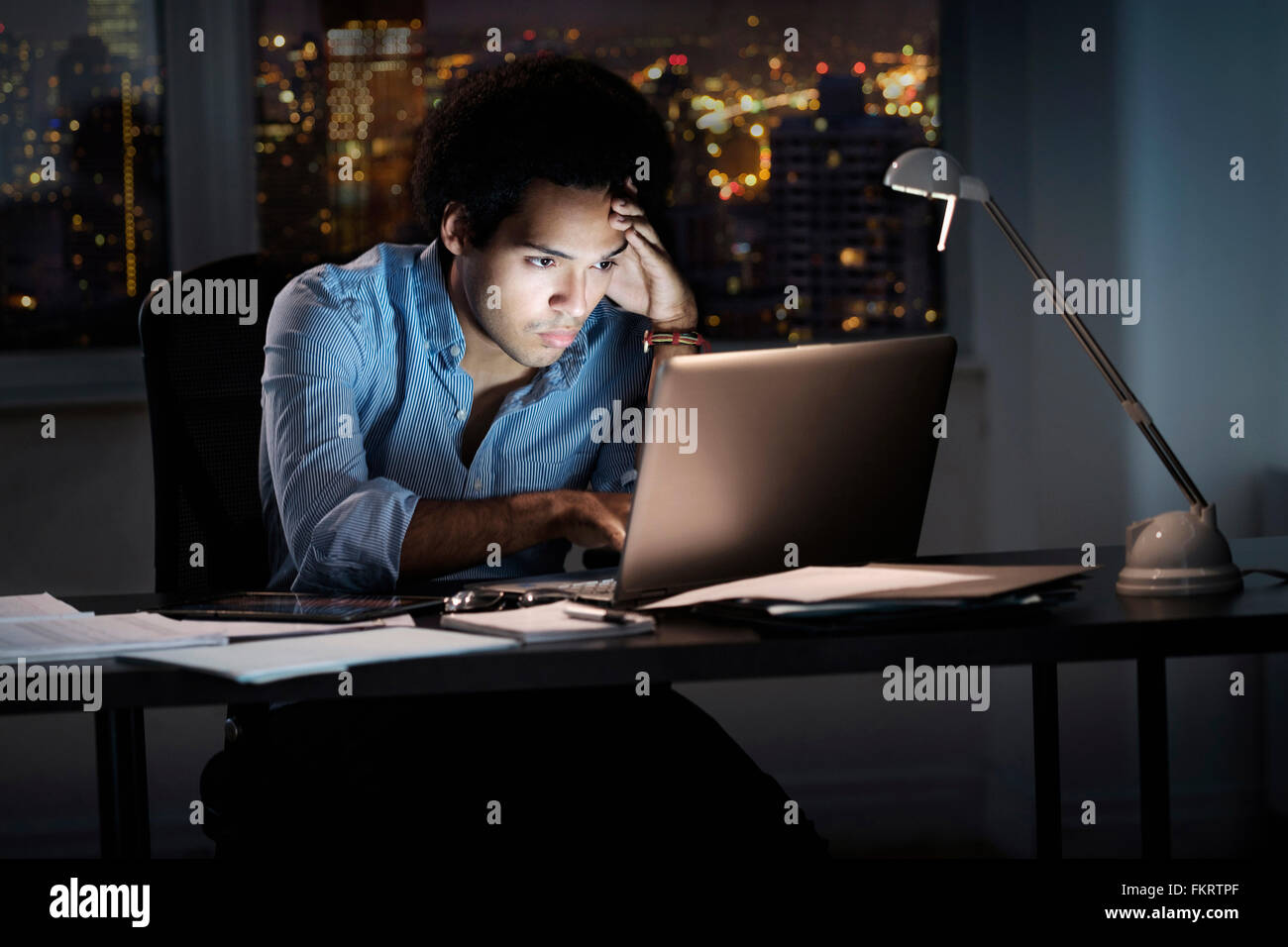 Empresario de raza mixta trabajando tarde en la oficina Foto de stock