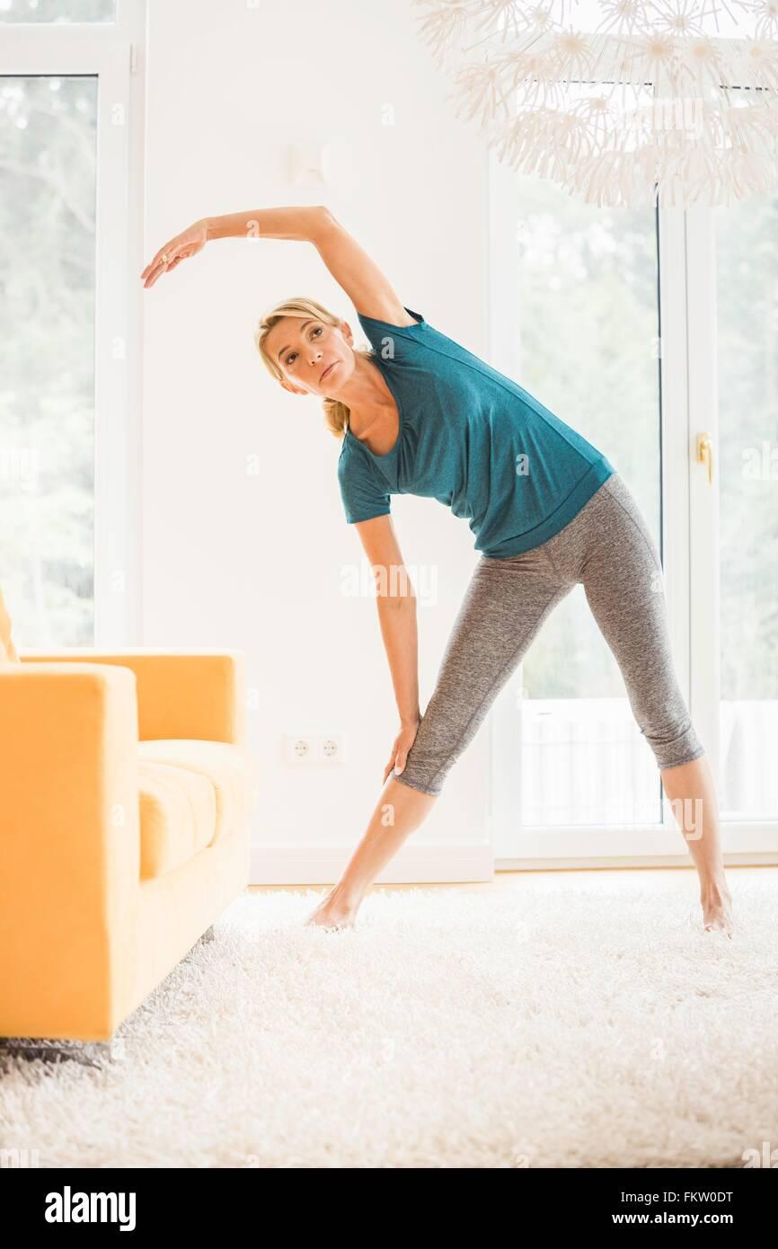 Mujer madura inclinarse lateralmente durante el ejercicio en la sala de estar Imagen De Stock