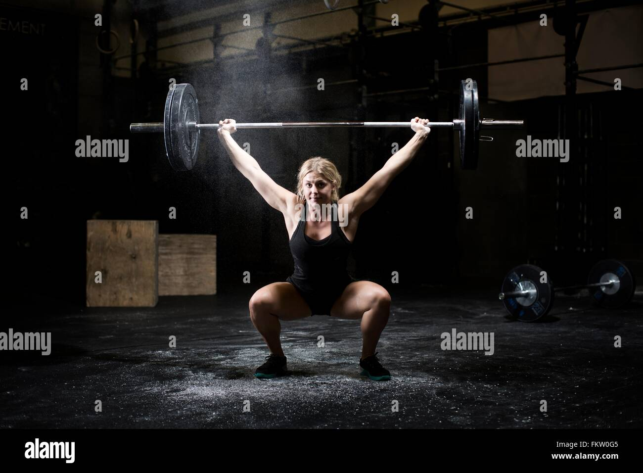 Mujer joven halterofilia barbell en gimnasio oscuro Imagen De Stock