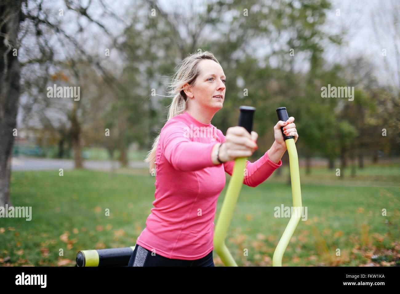 Mujer joven formación sobre máquina de ejercicio en el parque Imagen De Stock