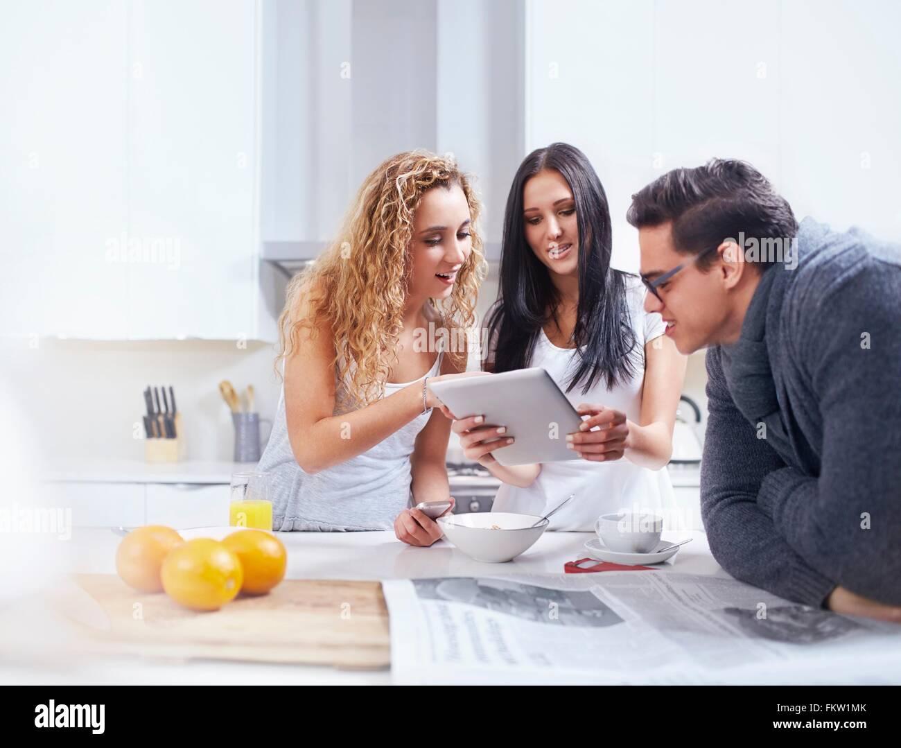 Tres jóvenes adultos mediante tableta digital en la cocina Imagen De Stock