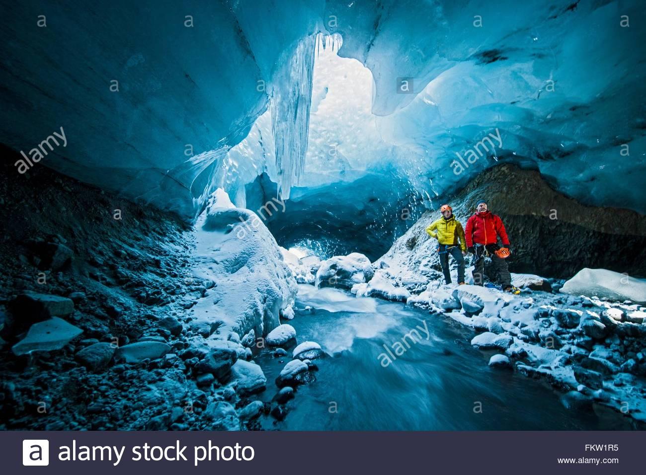 Retrato de dos hombres en la cueva de hielo debajo del glaciar Gigjokull Thorsmork, Islandia Imagen De Stock