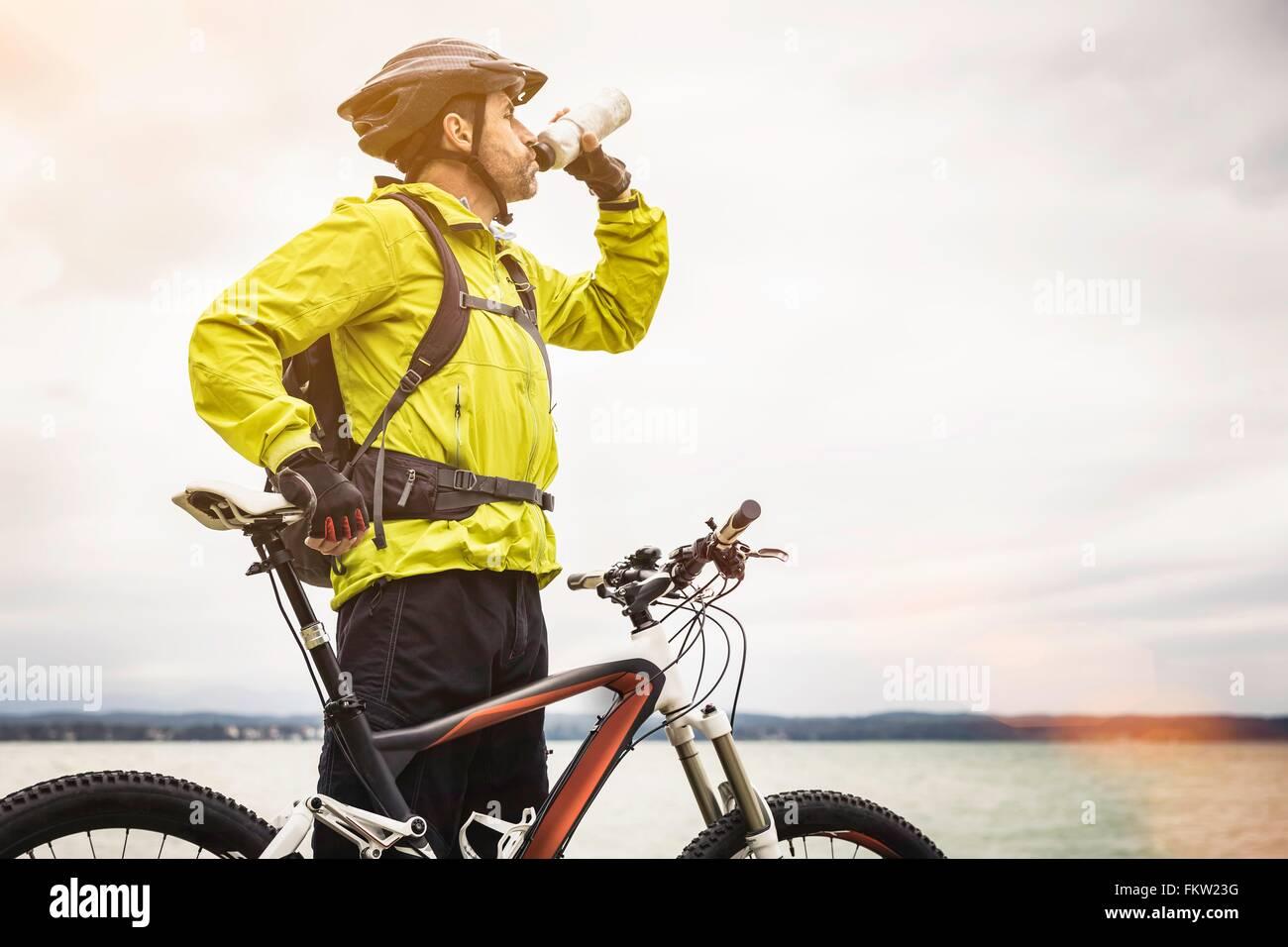 Macho maduro ciclista de montaña de agua potable en lakeside Imagen De Stock