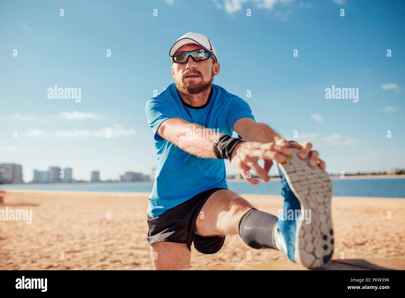Mitad hombre adulto en la playa de la pierna levantada de tocar los dedos del pie estiramiento, Dubai, Emiratos Árabes Unidos. Foto de stock