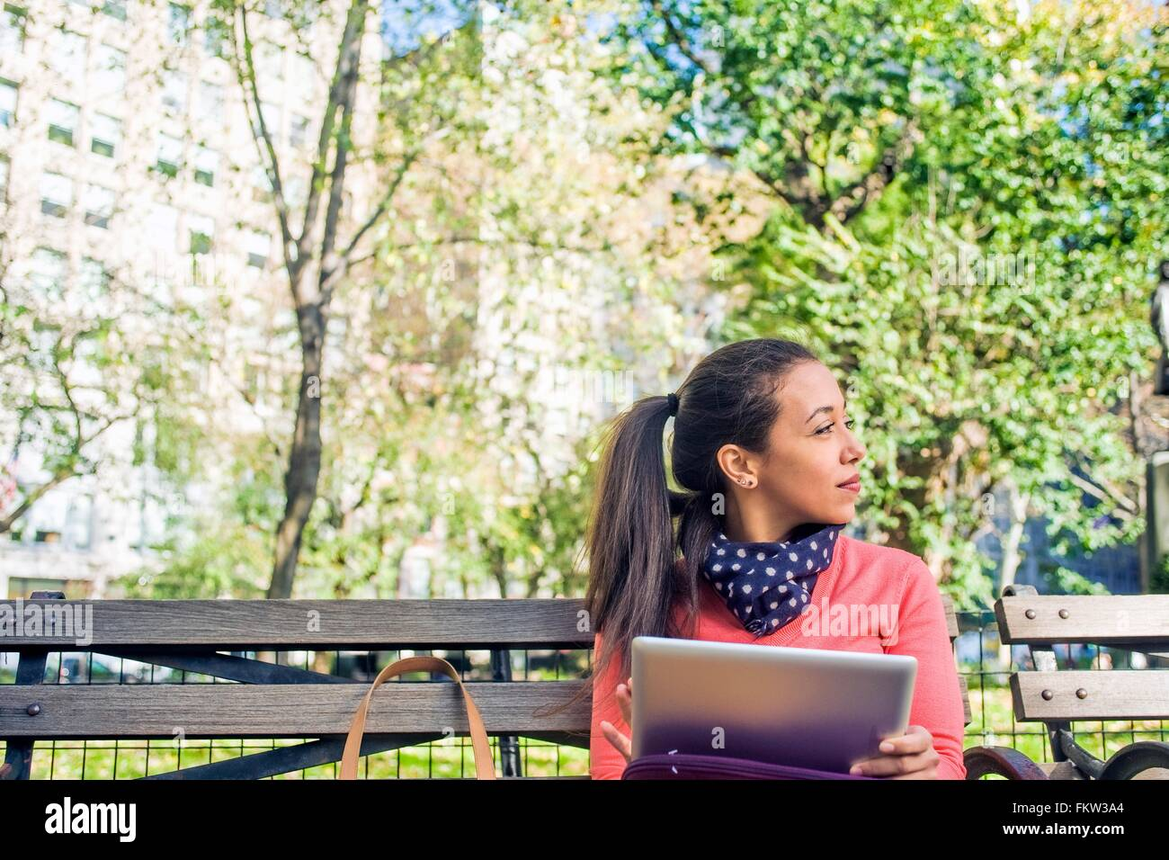 Mujer joven busca lateralmente desde un banco del parque mientras utilizando tablet digital Foto de stock