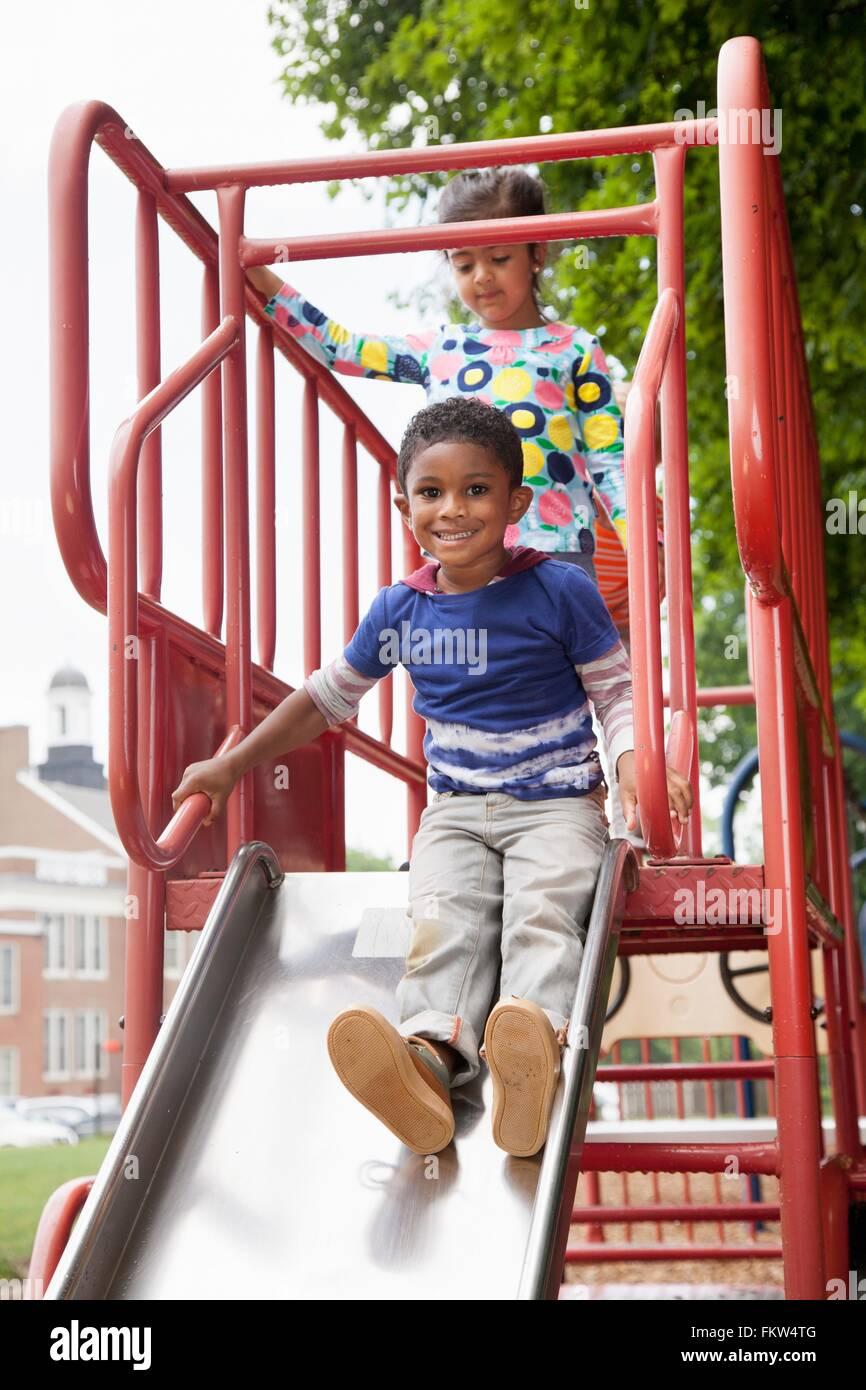 Chico y amigos deslizándose sobre playground diapositiva Imagen De Stock