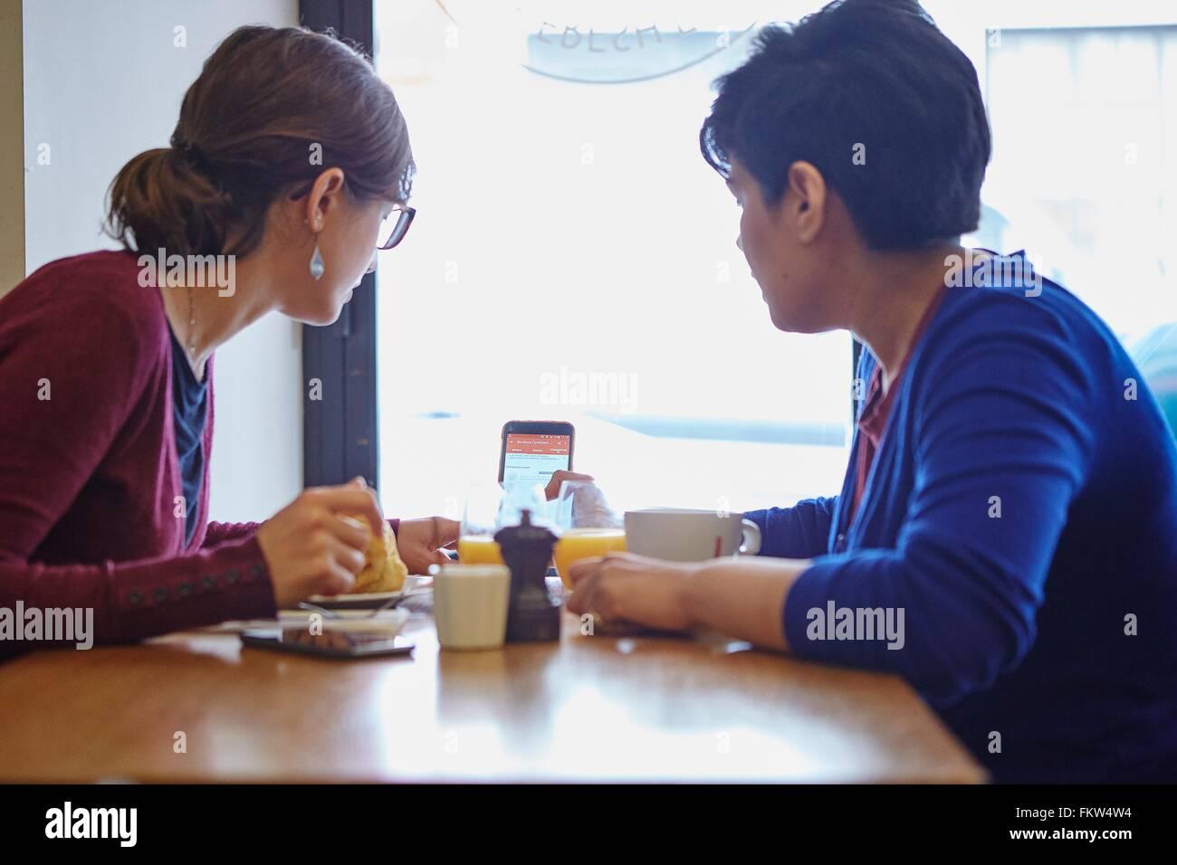 Dos mujeres leer texto smartphone en restaurante. Imagen De Stock