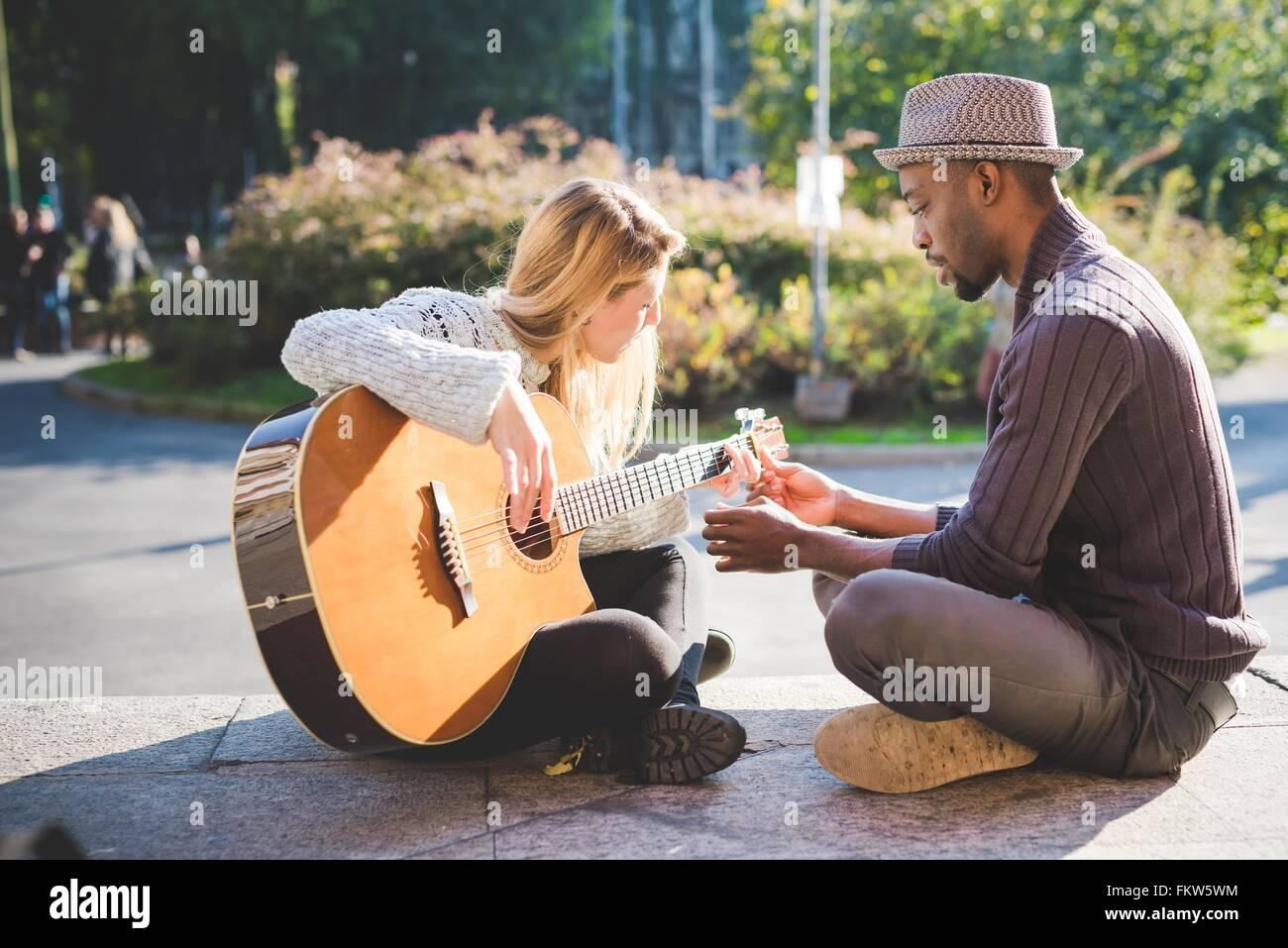 Par de aprender a tocar la guitarra en el parque Imagen De Stock