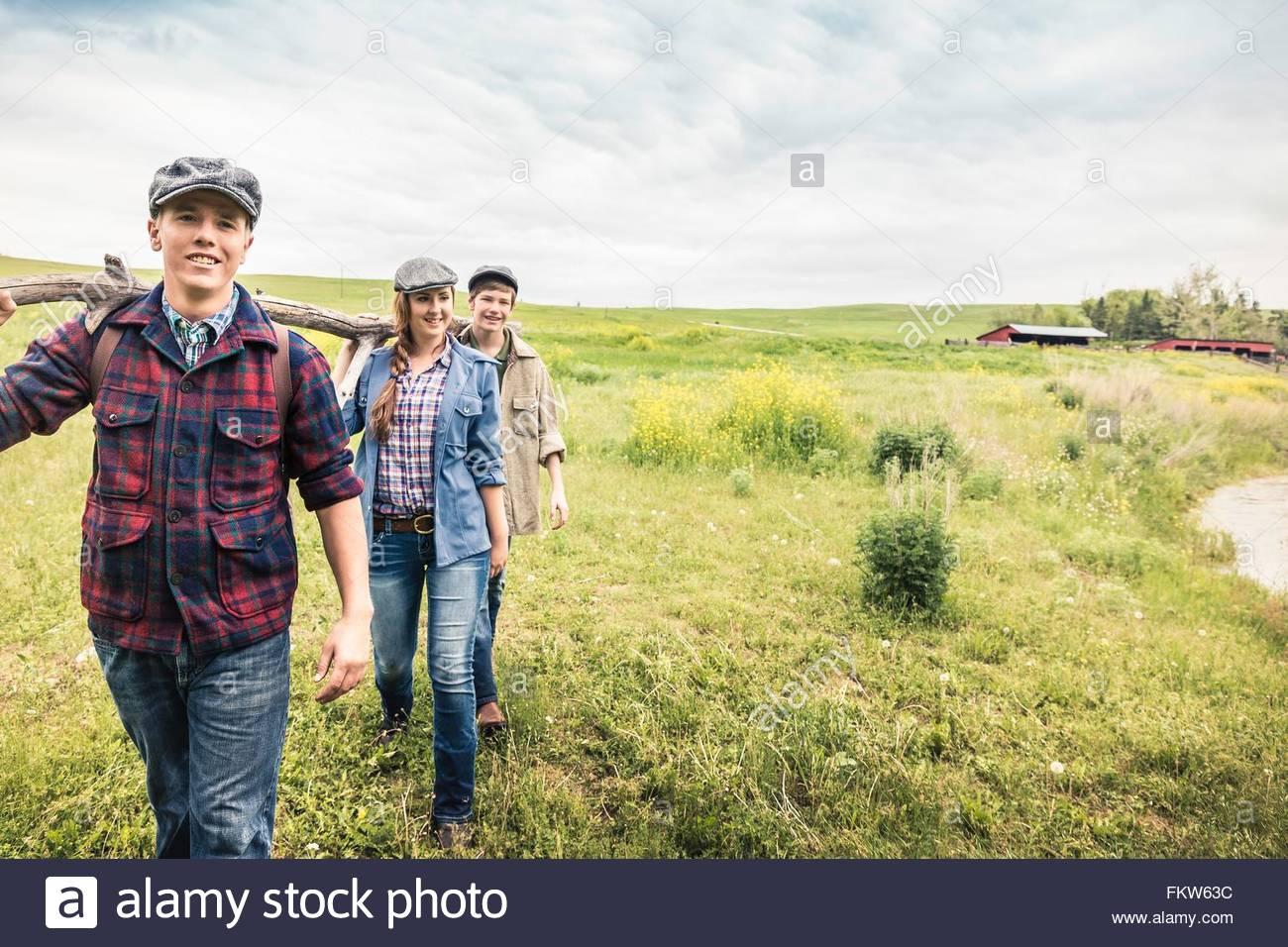 Adultos Jóvenes y jovencito llevando rama sobre el hombro sonriendo mirando a la cámara Imagen De Stock