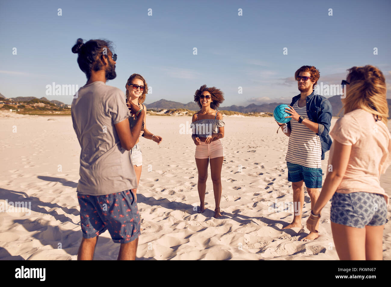 Grupo de jóvenes parados en círculo en la playa y jugando con la pelota. Jóvenes amigos jugando juego Imagen De Stock