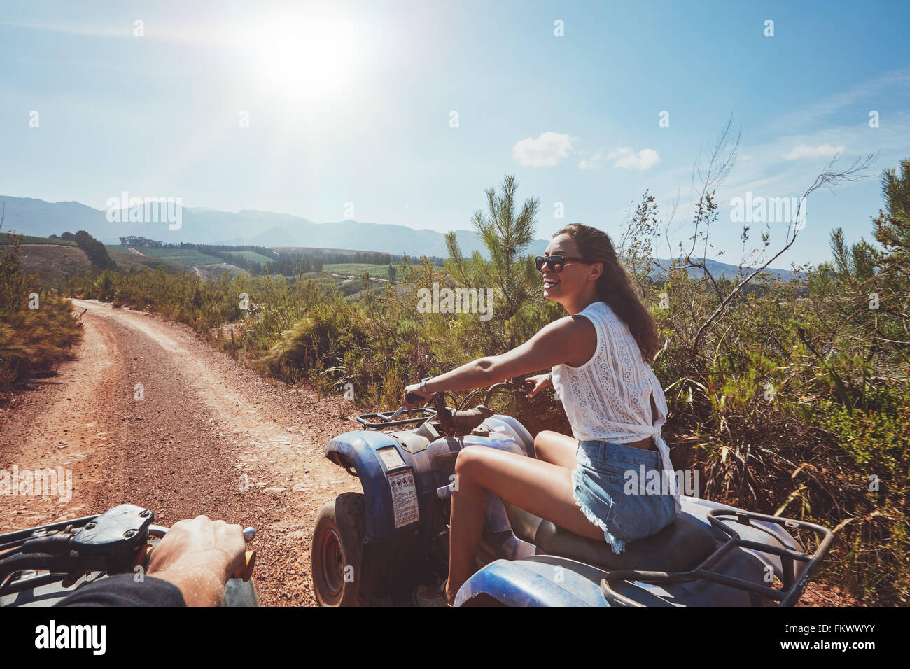 Mujer joven en quad por un sendero. Mujer joven de conducción de vehículos todo terreno en la naturaleza Imagen De Stock