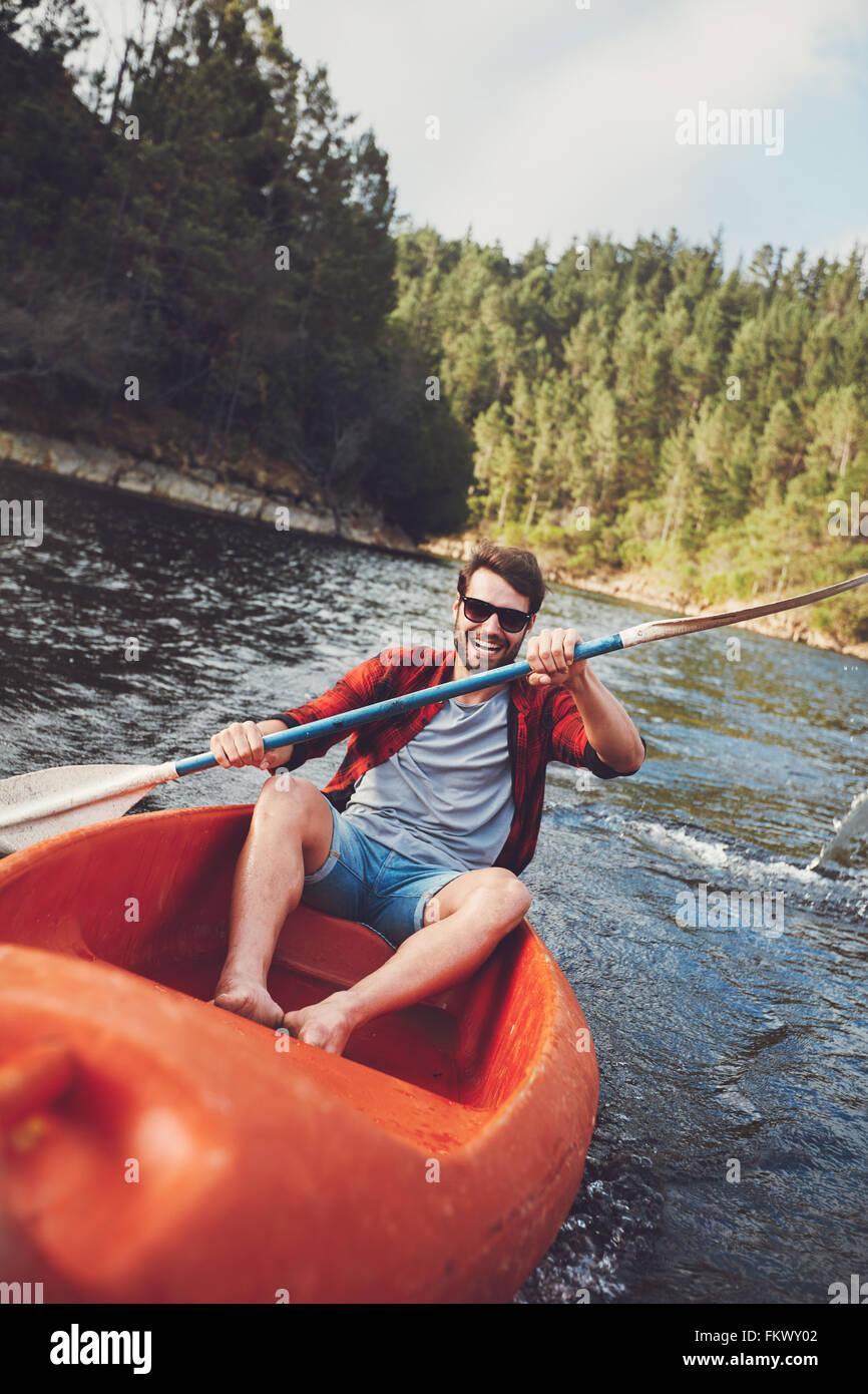 Retrato del joven sonriente remar en kayak en un lago. Joven canoa en un lago. Imagen De Stock