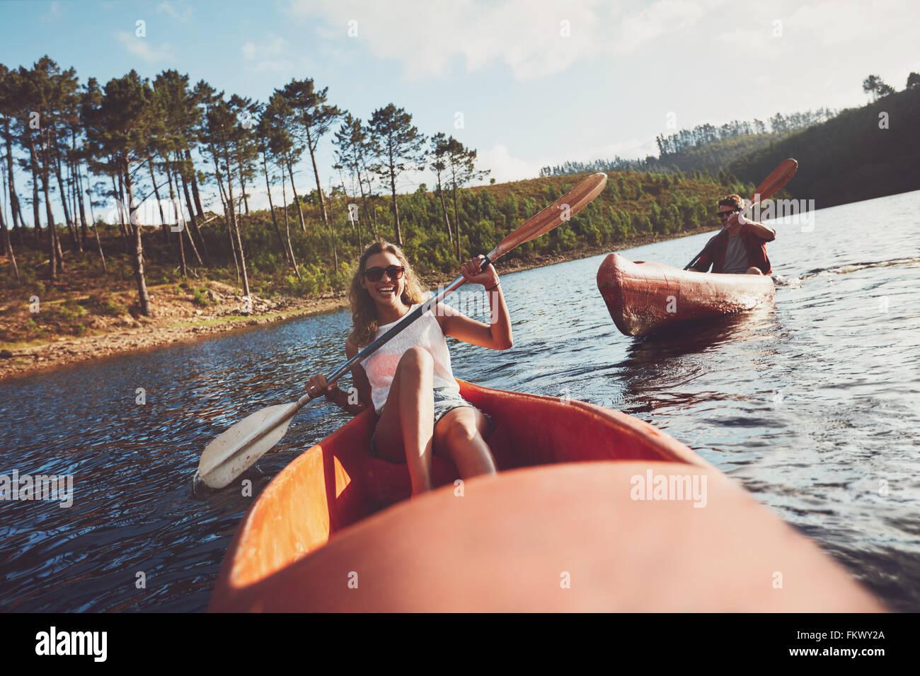 Los jóvenes en kayak en un lago. Mujer sonriente con un hombre kayakistas remando kayak en el fondo. Imagen De Stock