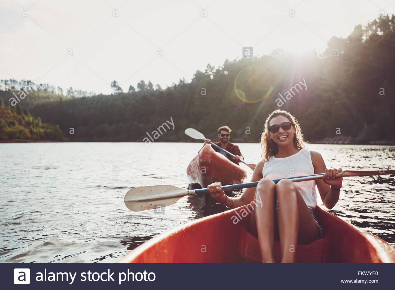 Feliz joven remando en un lago con su novio remando en la espalda. Feliz pareja joven canoa en verano. Imagen De Stock