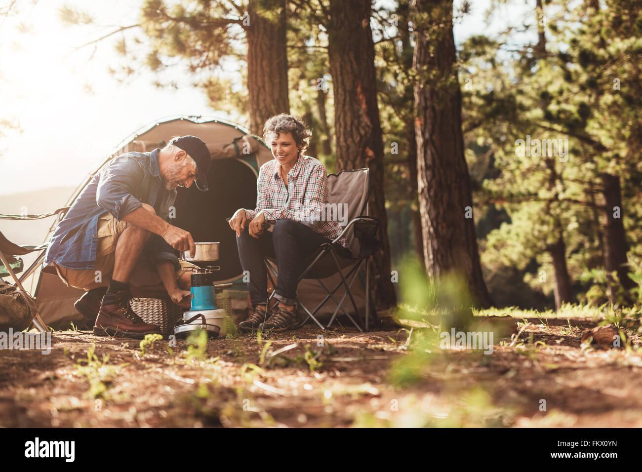 Campistas felices al aire libre en el desierto y hacer el café en una estufa. Las parejas ancianas en un camping Imagen De Stock