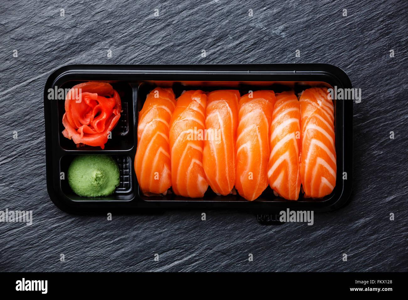 Sushi nigiri de salmón en una caja de plástico de embalaje en bandeja de piedra negra de fondo de pizarra Imagen De Stock