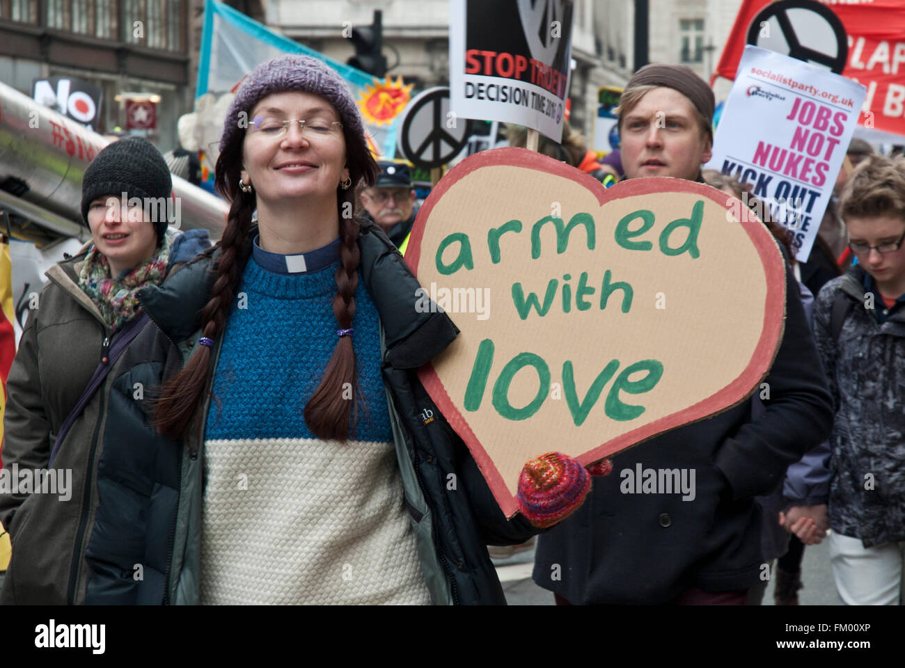 Vicario una mujer sonriente con pancartas caseras 'armado con amor' contra el tridente, demostración Imagen De Stock