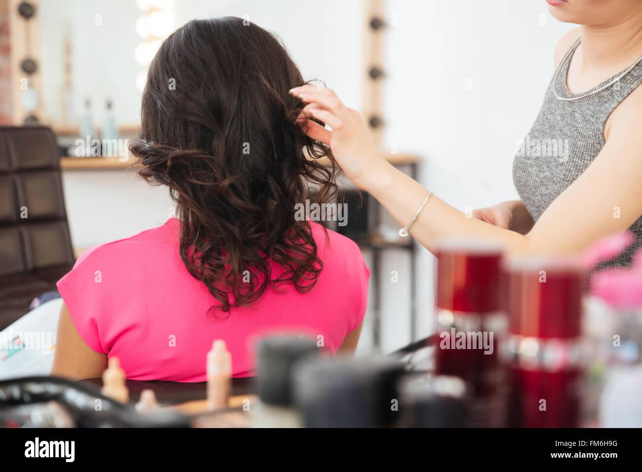 Vista posterior de la clienta con el cabello oscuro y peluquería haciendo peinado en el salón de belleza Imagen De Stock