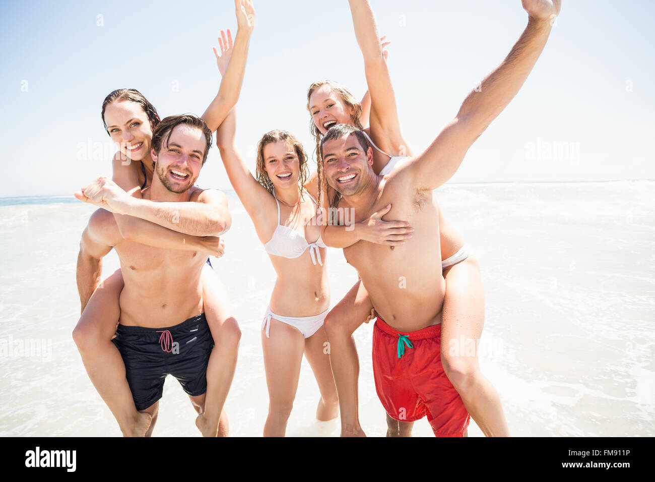 Los hombres dando un piggy back a las mujeres en la playa Imagen De Stock