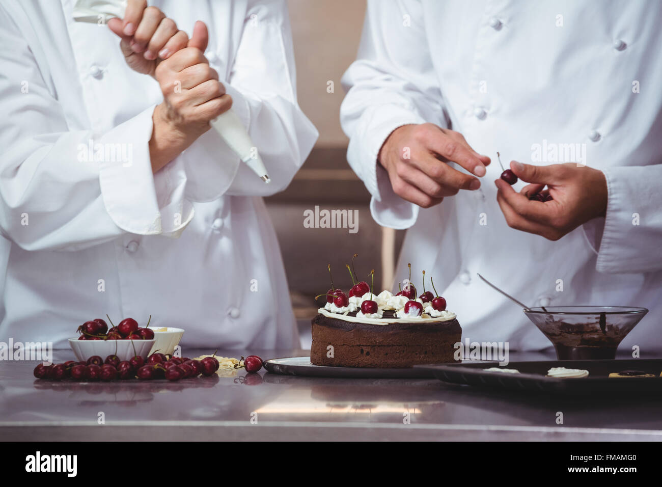 Los chefs decorar un pastel que acaba de hacer Imagen De Stock