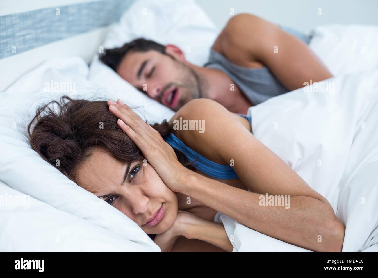 Mujer bloqueando los oídos con las manos mientras el hombre ronquidos en la cama Imagen De Stock