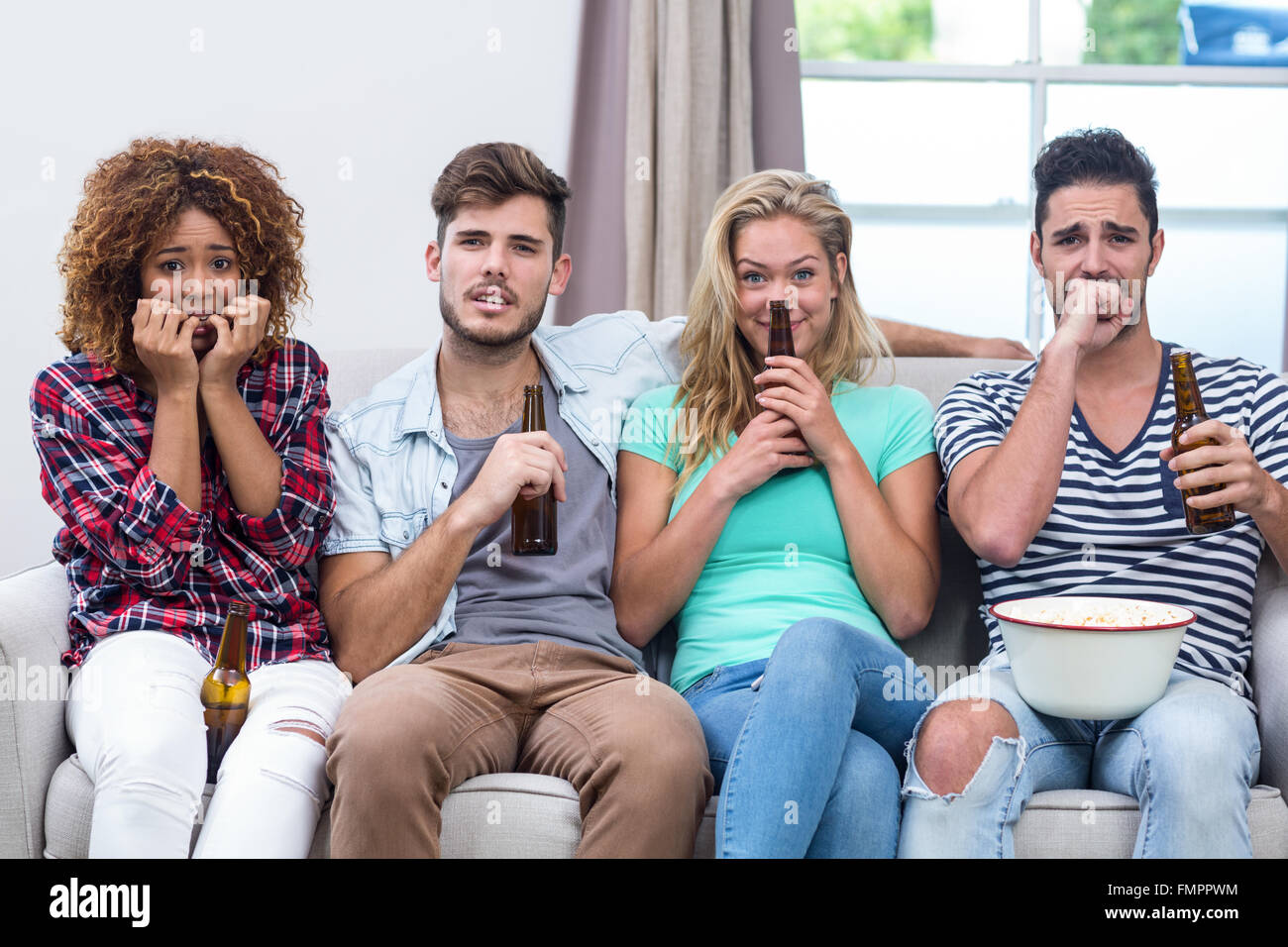 Multi-étnica nervioso amigos viendo la televisión en casa Imagen De Stock