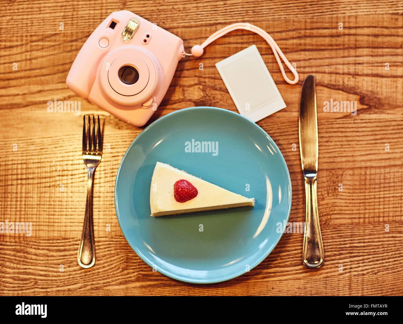 Placa con pastel de pie sobre la mesa cerca de la cámara fotográfica Imagen De Stock