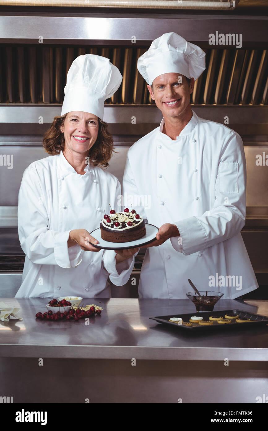 Los chefs presentando la torta que acaba de hacer Imagen De Stock