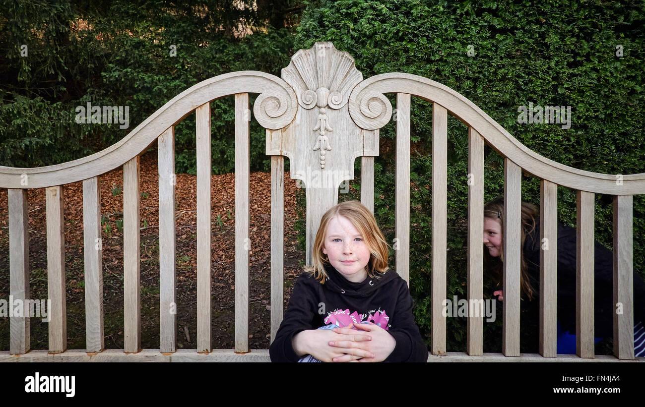 Una joven posando en un banco, su hermana se arrastra detrás listo para asustarla. Foto de stock
