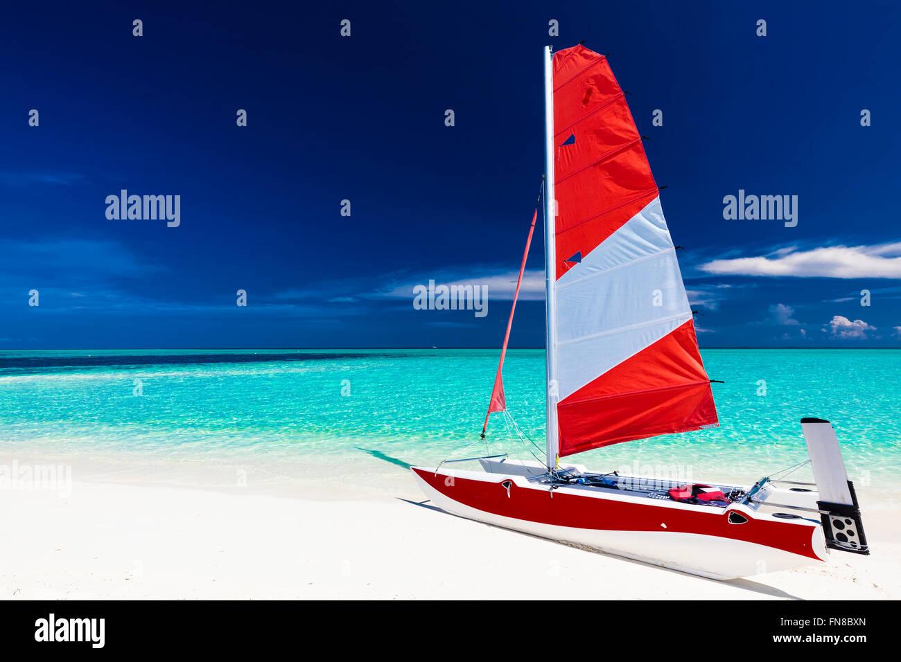 Velero con Red Sail en una playa de isla desierta con poca agua azul Imagen De Stock